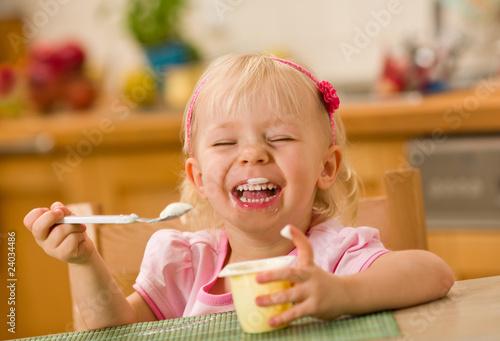 Fototapeta little girl eating yoghurt obraz