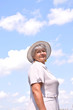 Middle-aged woman in a hat against the sky