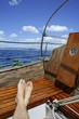 man feet relax on golden wooden old sailboat
