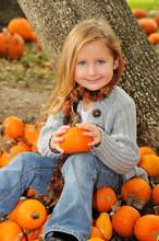 Little Blonde Girl Holding A Pumpkin In Pumpkin Patch In Fall