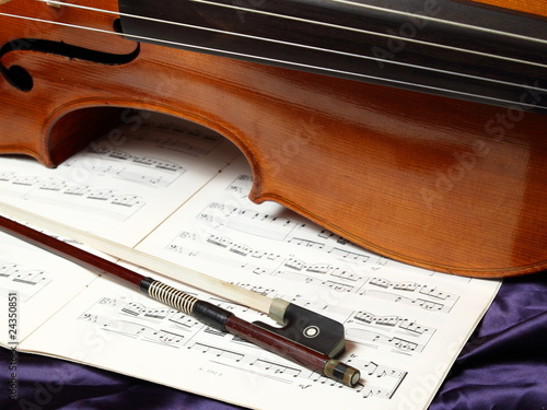 Cello bow and antique cello on opened sheet music - Buy this