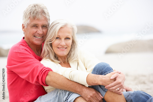 Fotografiet  Senior Couple On Holiday Sitting On Winter Beach