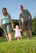 junge familie spaziert im garten ihres eigenheims