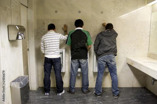 Obraz na plátně three men stading up, peeing in the bathroom
