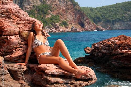 Obraz Dziewczyna na skalistej plaży - fototapety do salonu
