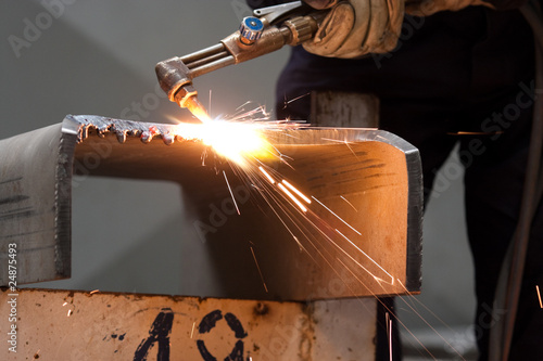 worker inside factory cut metal using blowtorch Wallpaper Mural