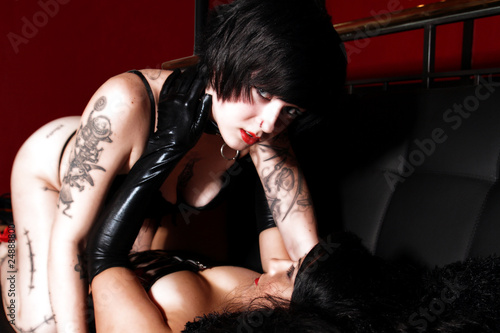Photo  Two young models with tattoos in lingerie and corset embracing