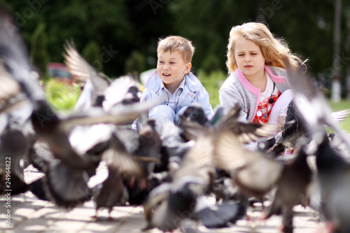 Children playing with doves in the city street