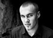 Młody przystojny mężczyzna z poważną miną w czerni i bieli