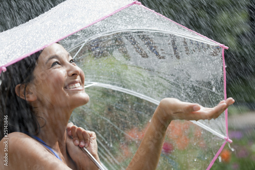 Fotografie, Obraz  Young Woman Using an Umbrella in Rain