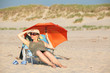 canvas print picture - Pregnant woman, lying on the beach.