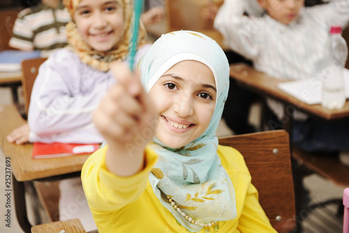 Photo  Adorable Muslim girl in classroom with her friends