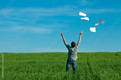 Photo young man throwing a paper in the green field