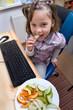 Mädchen am Computer mit Obst