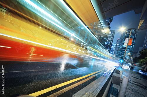 Photographie  Long exposure shot of blurred bus speeding through night street