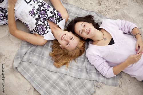 Fototapeta Two beautiful girls lying on sand. obraz na płótnie