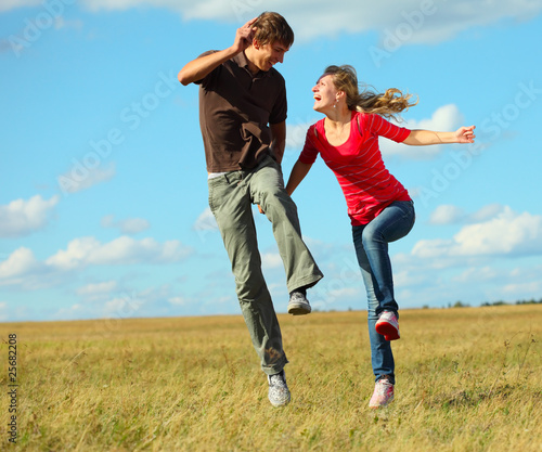 Young laughing couple jumping on meadow holding each other hands Wall mural