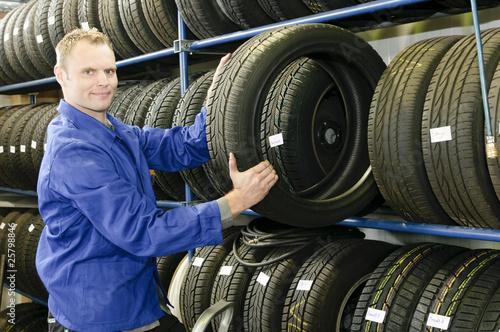 Fotografia, Obraz  Autowerkstatt Mann im Reifenlager holt Reifen