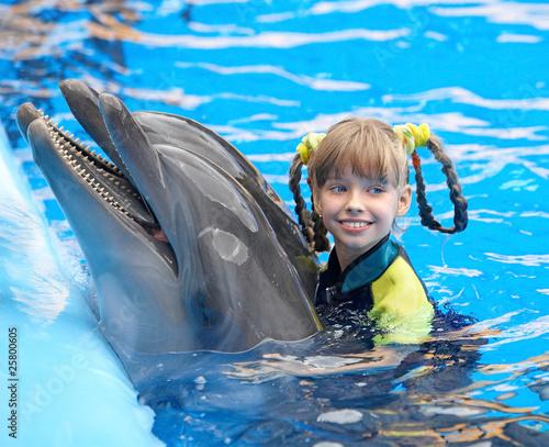 Plakat Dziecko i delfin w błękitnej wodzie.