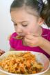 Mädchen isst Nudeln mit Wurstgulasch
