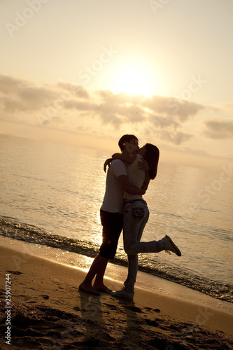 Fototapety, obrazy: Couple kissing in sunrise at the beach.