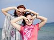 Two girlfriends at the beach show binocular