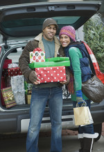 Couple Posing With Christmas Gifts By Car