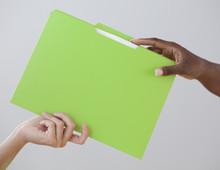African Woman Handing Co-worker A Folder