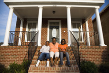 """African Mother, Daughter And Son Sitting On Front Stoop Of House"""