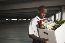 African Businessman Carrying Personal Belongings