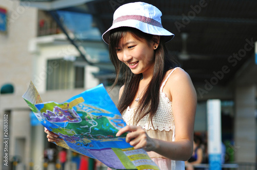 Foto  Little Chinese Asian Tourist Girl looking at her map