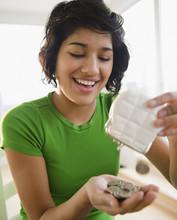 Hispanic Woman Emptying Coin Purse