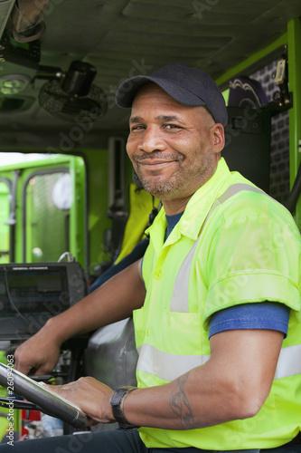 African American man driving garbage truck