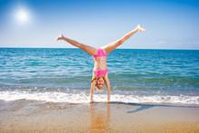 Schoolgirl Making Gymnastics On Seashore