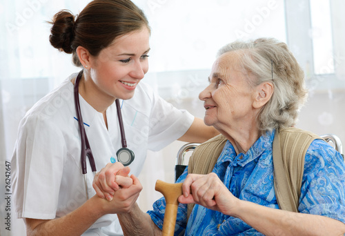 Fotografia  Senior woman is visited by her doctor or caregiver