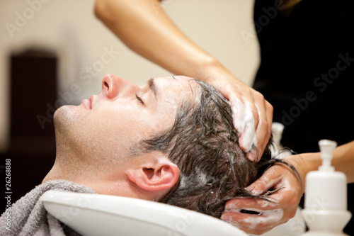 Handsome man shampooed by his hairdresser