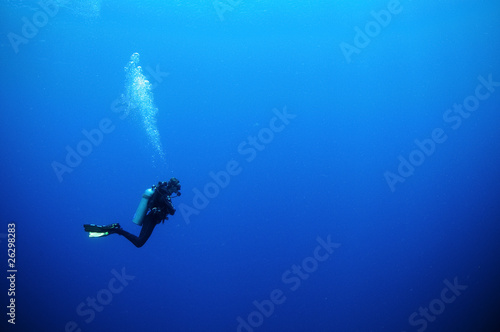 Photo scuba diver in deep blue water