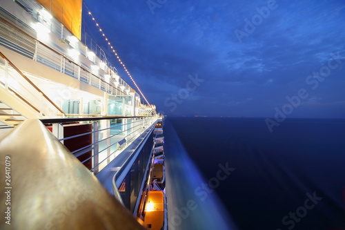 Fotomural big illuminated cruise ship riding in evening. wide angle.