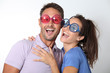 Couple wearing colored glasses having fun on white background