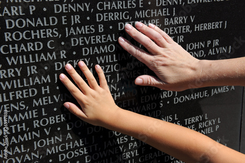 Fotografía  Hand of Adult and Child Touching Names at War Memorial