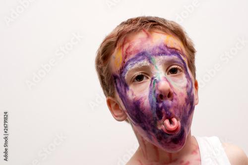 Vászonkép bambino con viso mascherato e linguaccia