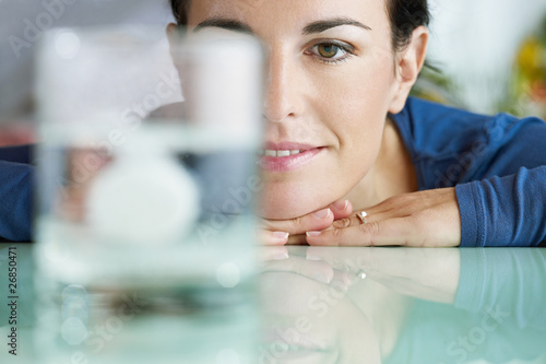 Photo woman looking at aspirin in glass of water