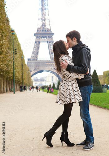 Photo  Young romantic couple kissing near the Eiffel Tower in Paris