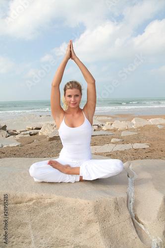 Beautiful blond woman practising yoga at the beach