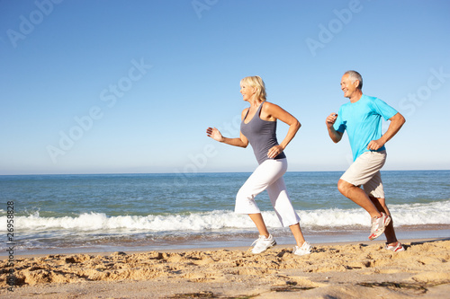 Poster Jogging Senior Couple In Fitness Clothing Running Along Beach