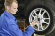 Mann macht Reifenwechsel in der Autowerkstatt