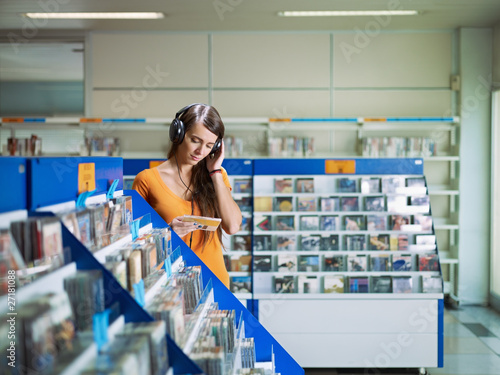 Wall Murals Music store girl listening music in cd store