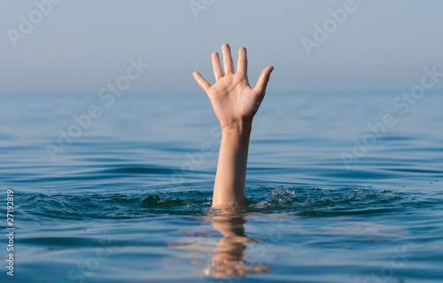 Fotografija single hand of drowning man in sea asking for help