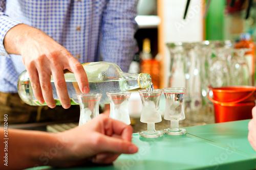 Barkeeper schenkt Schnaps in Gläser Fototapeta