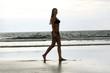 happy woman in bikini walks on a beach